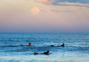 The super moon looms over surfers in Sydney, Australia