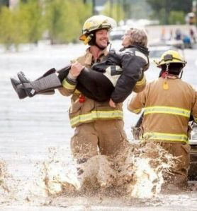Calgary fireman evacuating flood victims