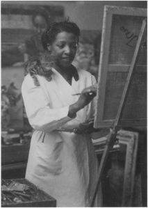 Loïs Mailou Jones painting in her Paris studio in 1937  with kitten supervising from her shoulder.