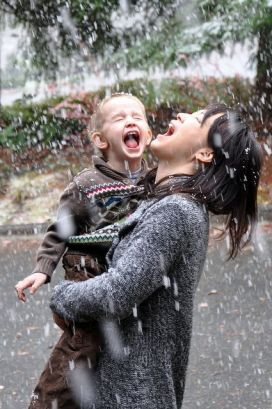 mother and child enjoying the rain