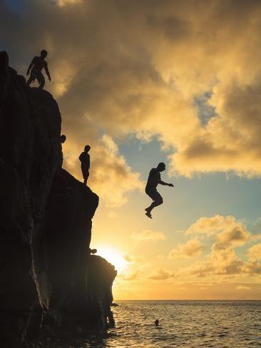 USA, Hawaii, Oahu, North Shore, Waimea Bay, Divers Jumping Off Cliff Photographic Print by Michele Falzone | Art_com